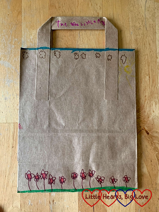 """A brown paper bag decorated with flowers along the bottom and the words """"The Three Little Pigs"""" on the handle"""