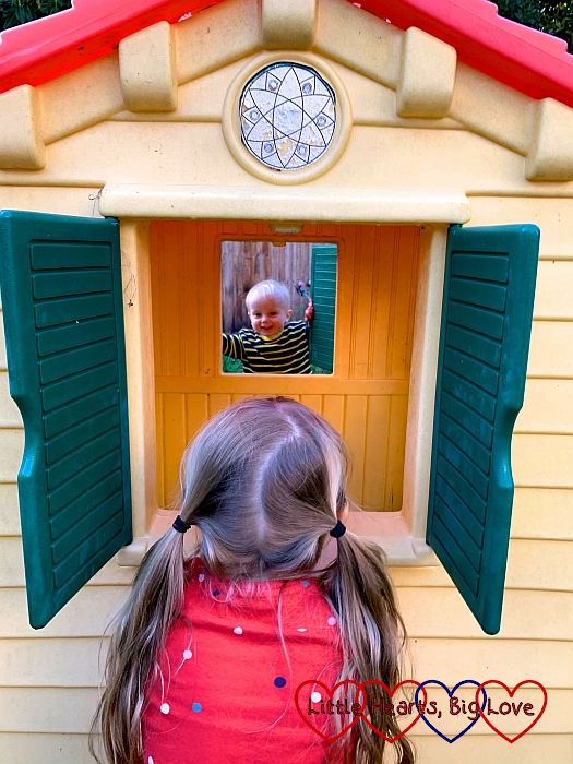 Sophie looking through the window of her playhouse with Thomas looking at her through the window on the other side of the house