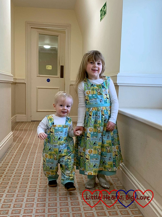 Thomas wearing dungarees and Sophie wearing a dress in matching green animal print abric