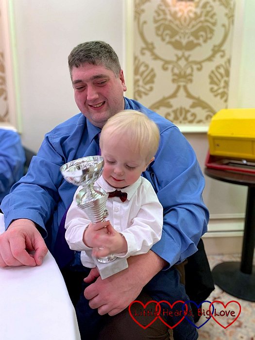 Thomas in his shirt and bow tie, holding his trophy while sitting on Daddy's lap