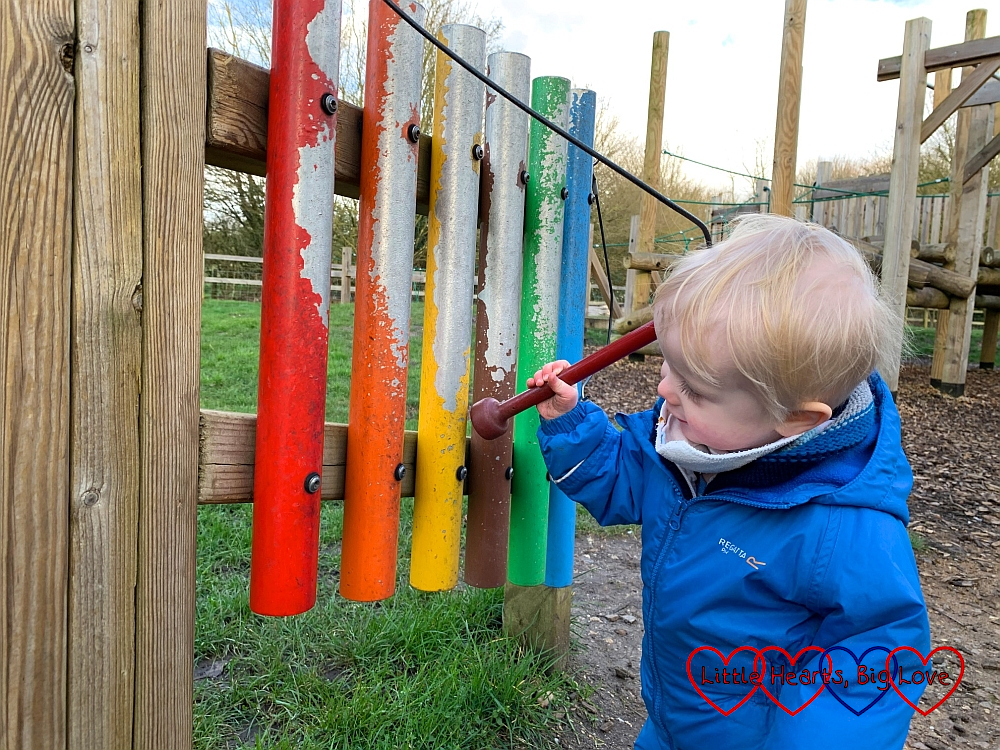 Thomas hitting the rainbow coloured chime bars at the park