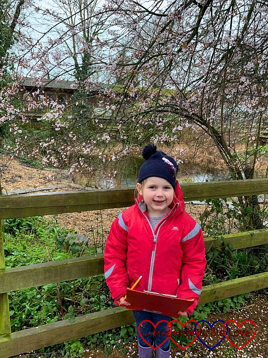 Sophie standing in front of a tree with pink blossom appearing on the branches