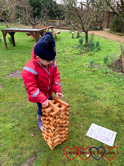 Sophie setting up the wooden blocks on a Jenga tower in the orchard at Iver Environment Centre