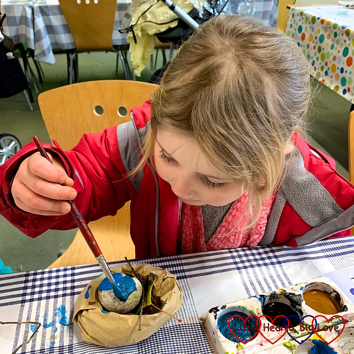 Sophie painting her rock egg with blue paint