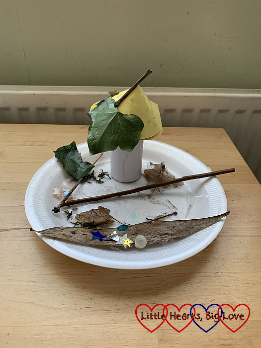 Sophie's fairy garden with a fairy house made from a cardboard tube and cone stuck to a polystyrene plate decorated with leaves
