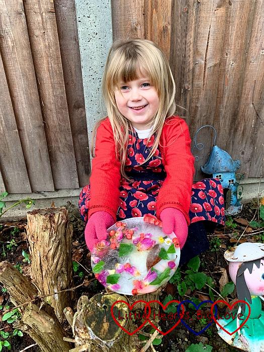 Sophie holding her frozen suncatcher on top of a tree stump