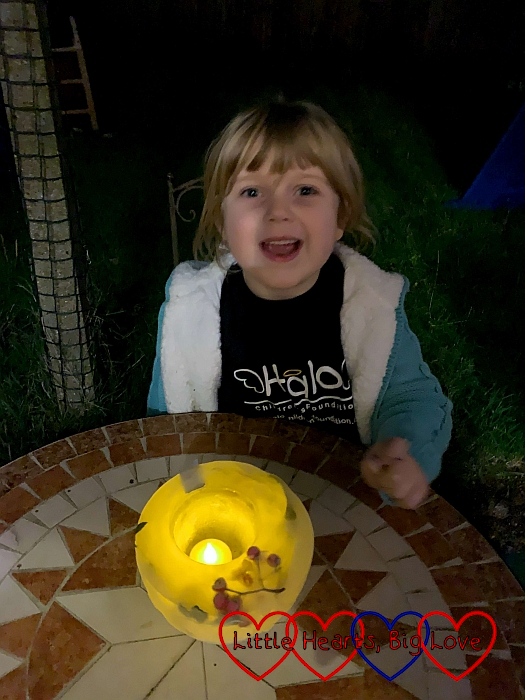 Sophie in the dark with her frozen ice lantern lit by a tea light