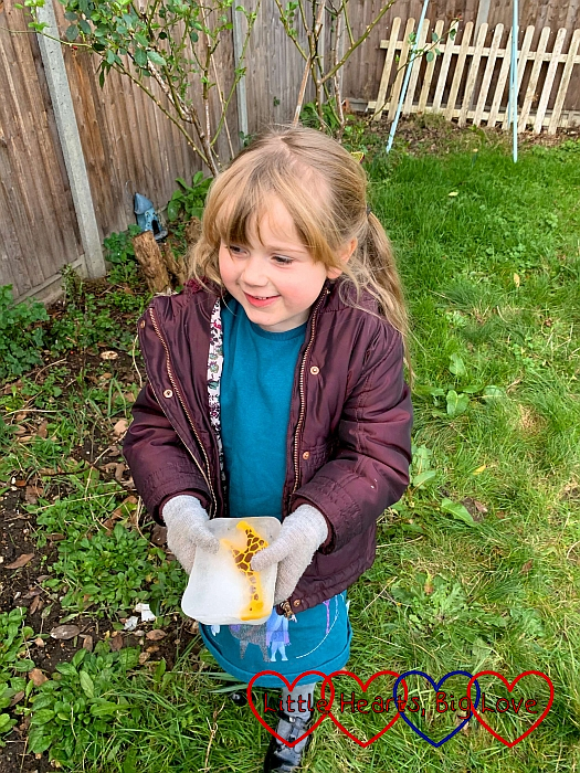 Sophie in the garden holding a frozen block of ice with a giraffe inside