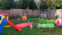 An obstacle course made of slides, play tunnels, a trellis and the toy house set up in the garden