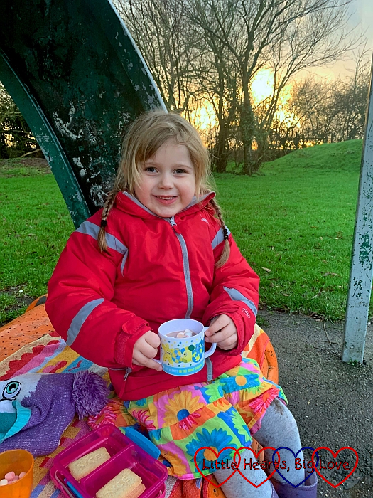 Sophie sitting on a bench at the park with a cup of hot chocolate