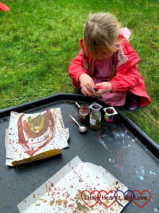 Sophie painting a rainbow and doing some splattering with mud paints