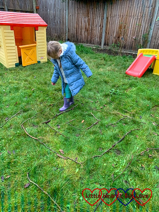 Sophie making her way around a maze marked out with sticks in the garden
