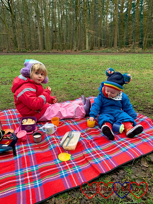 Sophie and Thomas wrapped up warm in winter coats and hats, sitting on a picnic rug at the park enjoying a picnic