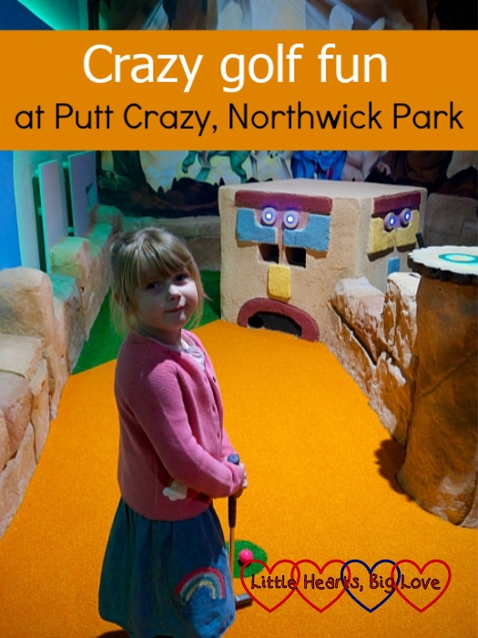 "Sophie holding her golf club and standing in front of a Mayan-themed cube on one of the holes at Putt Crazy – ""Crazy golf fun at Putt Crazy, Northwick Park"""