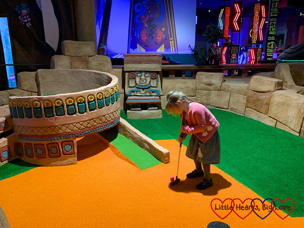 Sophie preparing to hit the ball up a slope into a Mayan-themed tower on the kids course at Putt Crazy