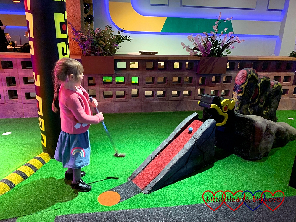 Sophie hitting a golf ball up a slope and into the mouth of a snake on the Putt Crazy Adults course