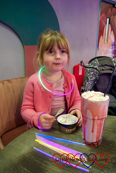 Sophie wearing a glow-stick necklace and sitting at a table eating ice cream with a big strawberry milkshake in front of her