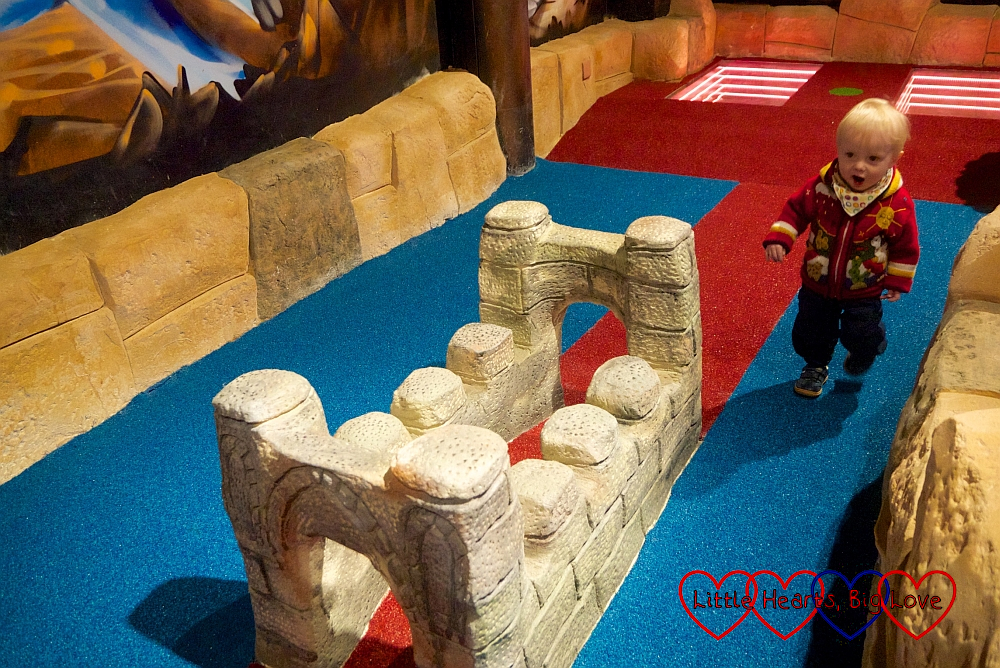 Thomas walking past a castle on one of the holes on the Putt Crazy Kids course