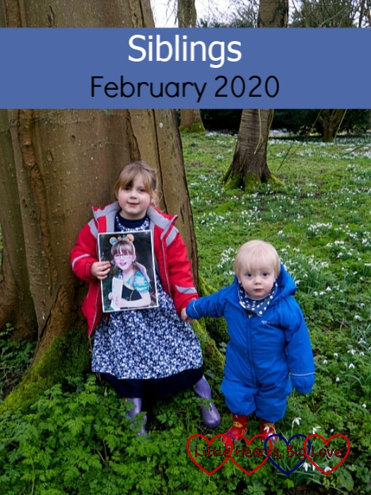 "Sophie standing leaning against a tree, holding a photo of Jessica in front of her, and Thomas's hand as he stands next to her with a field of snowdrops surrounding them - ""Siblings - February 2020"""