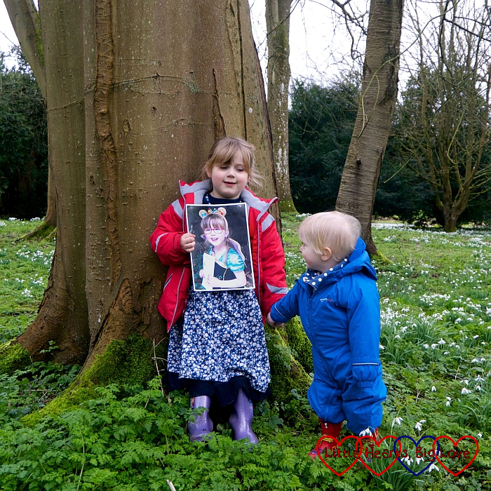 Sophie standing leaning against a tree, holding a photo of Jessica in front of her, and Thomas's hand as he stands next to her looking at the photo of Jessica, with a field of snowdrops surrounding them