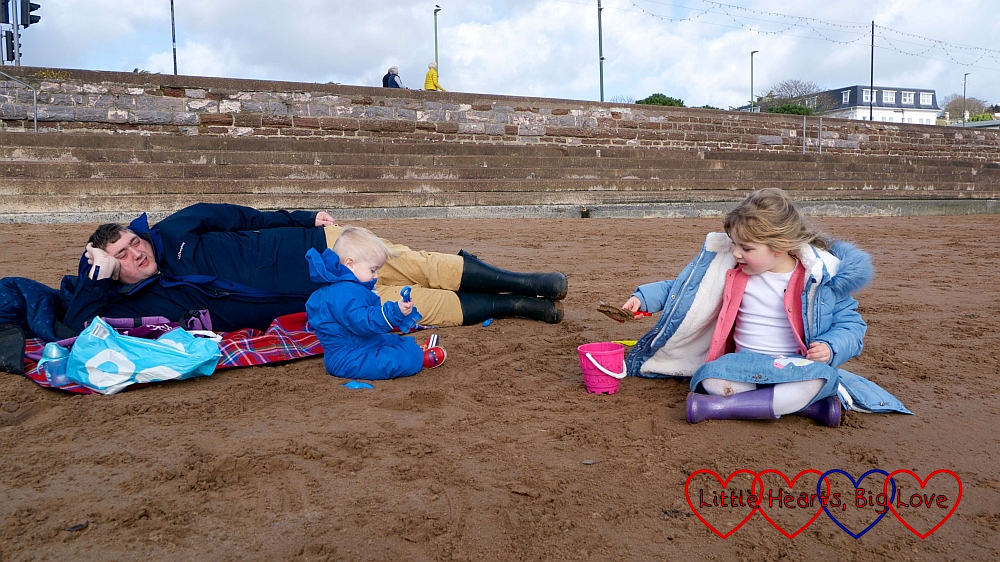 Hubby lying on the picnic blanket while Thomas and Sophie play in the sand on the beach