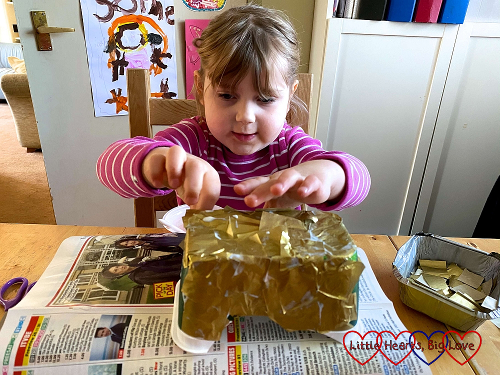 Sophie gluing squares of gold tissue paper to the outside of the margarine tub