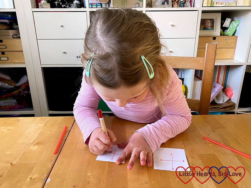 Sophie drawing red crosses on two squares of paper