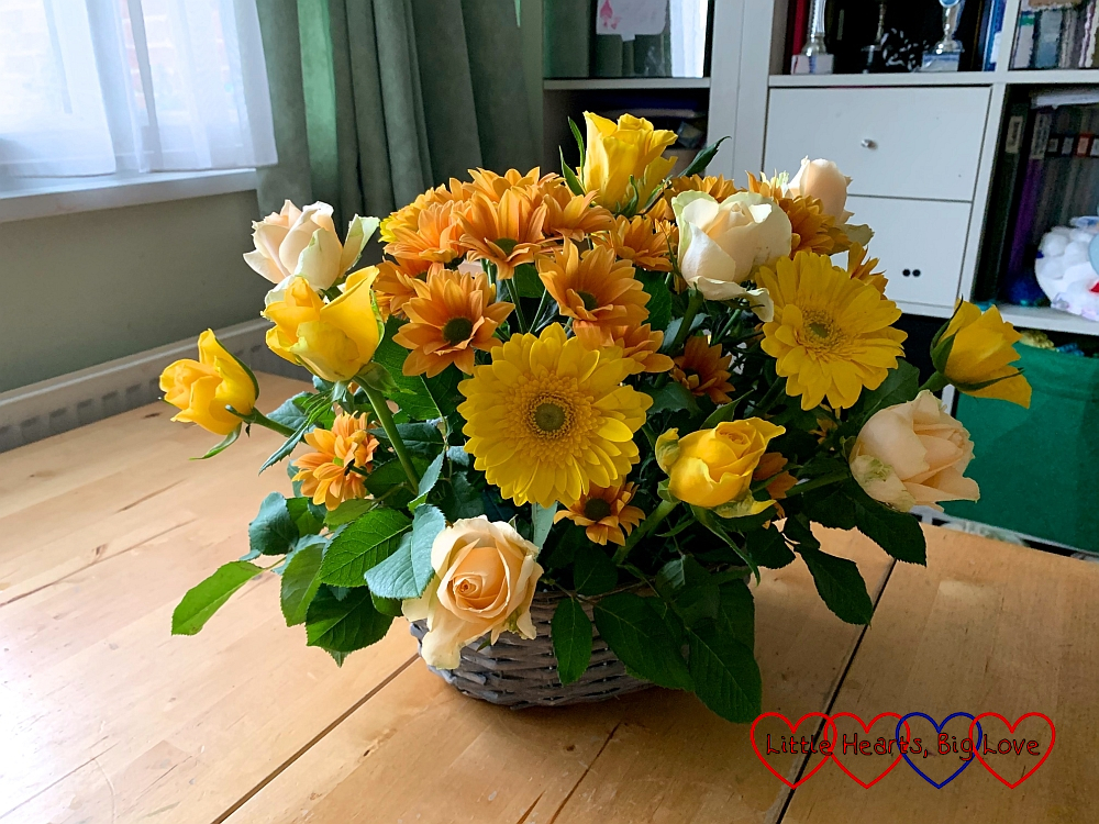 A flower arrangement with yellow roses, chrysanthemums and gerberas