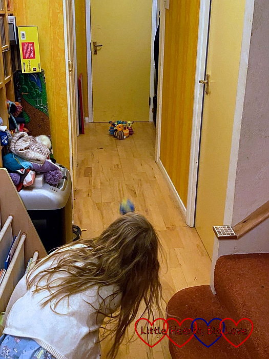 Sophie bowling a ball down our hallway towards some furry monster skittles