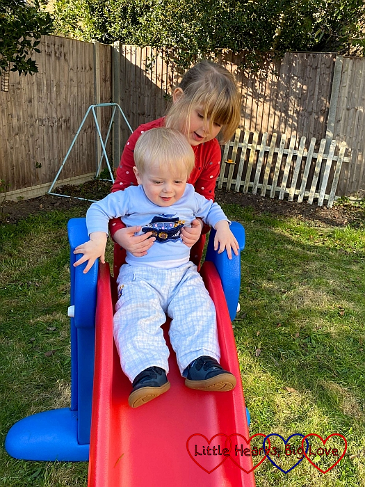Sophie helping Thomas go down the slide in the garden