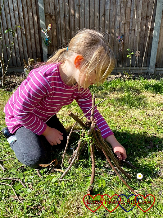 Sophie arranging twigs to make a miniature tepee
