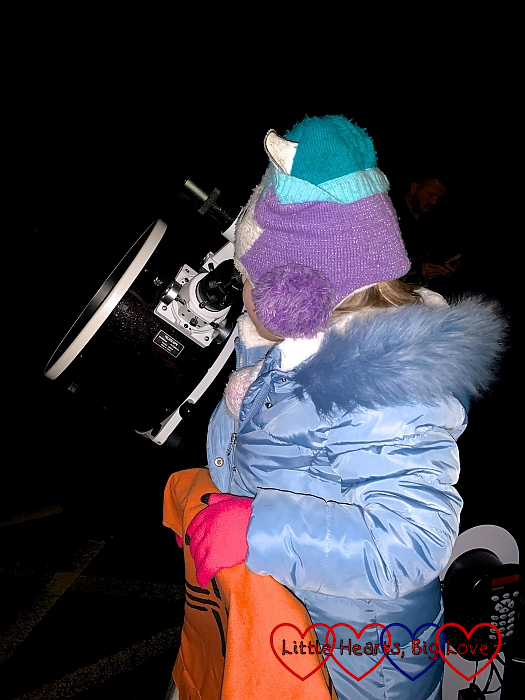 Sophie standing on a step stool, looking through a telescope