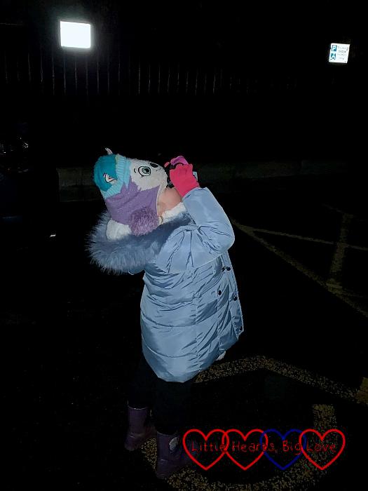 Sophie looking at the night sky through her binoculars