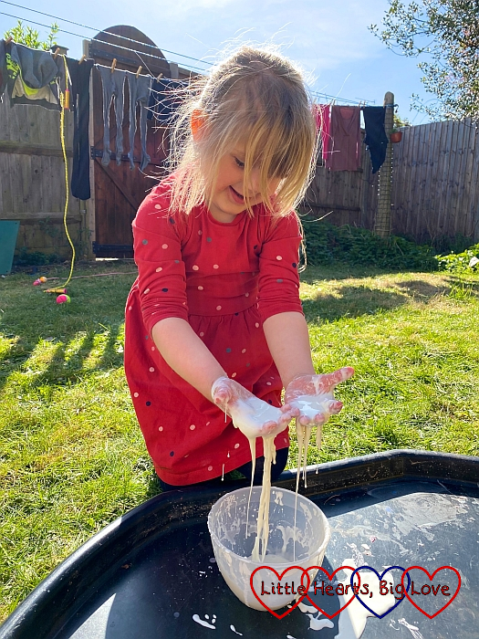Sophie letting the oobleck run through her fingers