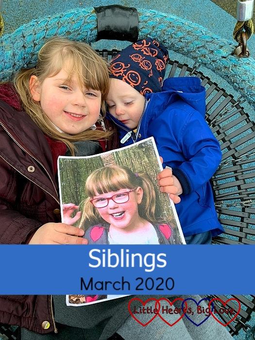 "Sophie and Thomas lying together in the spider swing at the park holding a photo of Jessica - ""Siblings - March 2020"""