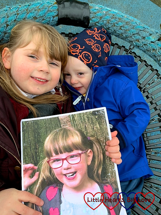 Sophie and Thomas lying together in the spider swing at the park holding a photo of Jessica