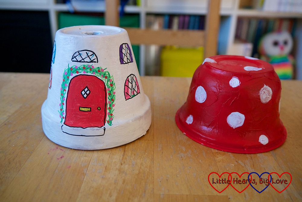 A plant pot painted white with doors and windows drawn on it and a yogurt pot painted red with white spots