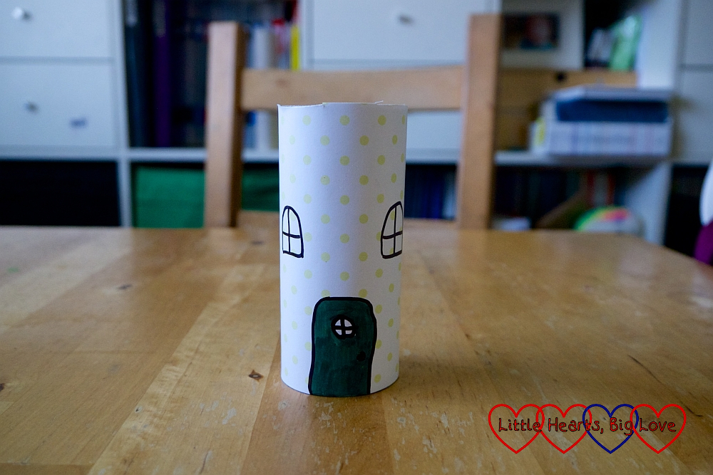 A toilet roll tube covered with patterned paper with a door and windows drawn on it