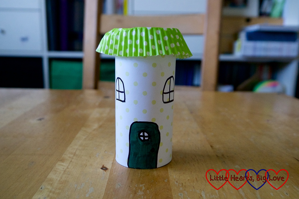 A toilet roll tube covered with patterned paper with a door and windows drawn on it and a cupcake case on top for the roof