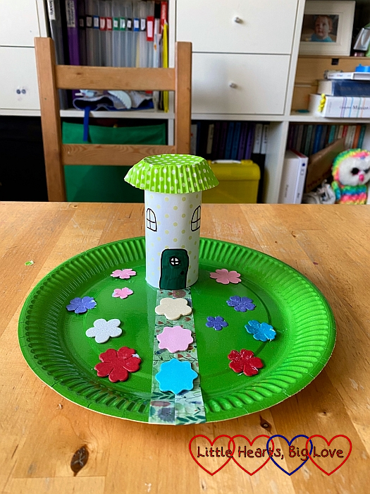 A fairy house made from a toilet roll tube glued to a green paper plate with foam flowers stuck to the paper plate