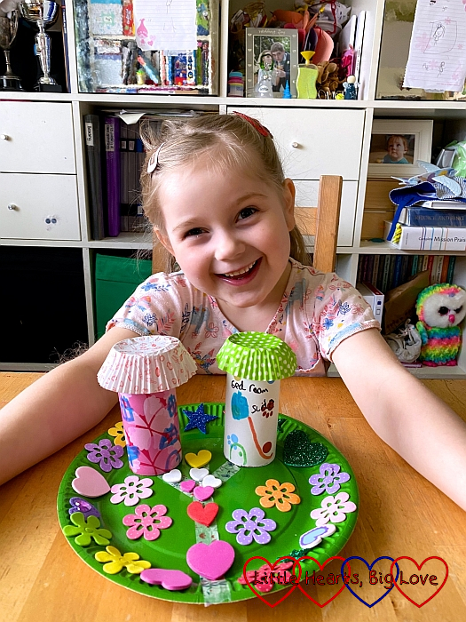 Sophie with her fairy garden with two toilet-roll fairy houses stuck to a green paper plate covered with foam flowers