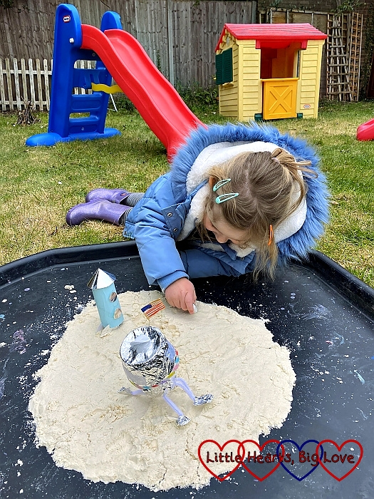 Sophie recreating with Moon landings on the tuff spot with a homemade rocket, lunar module and an astronaut on some moon sand