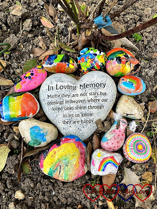 "Colourful painted pebbles around a heart stone which says ""In loving memory. Maybe they are not stars but openings in heaven where our loved ones shine through to let us know they are happy."""