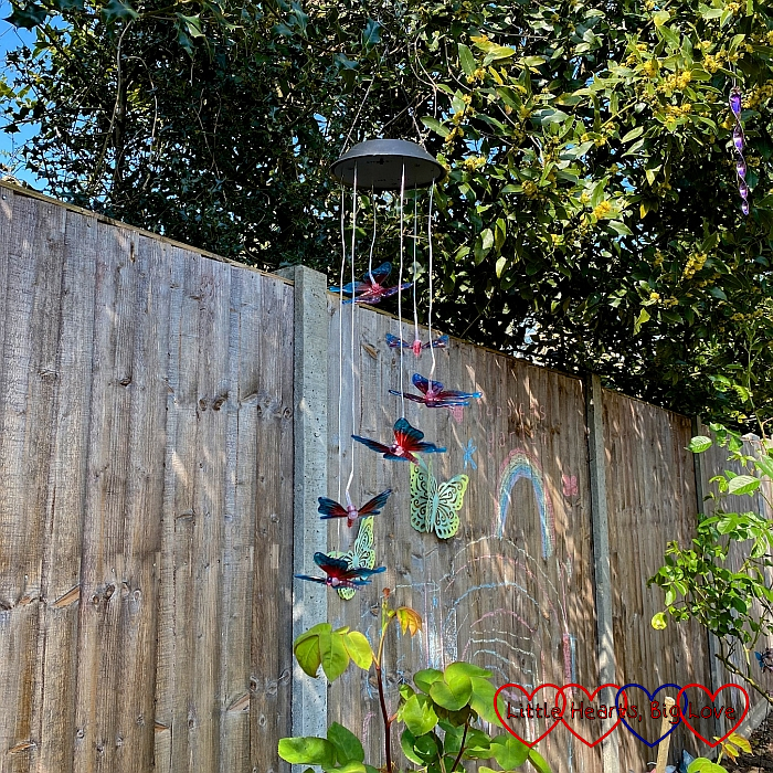A butterfly mobile hanging above the rose bushes