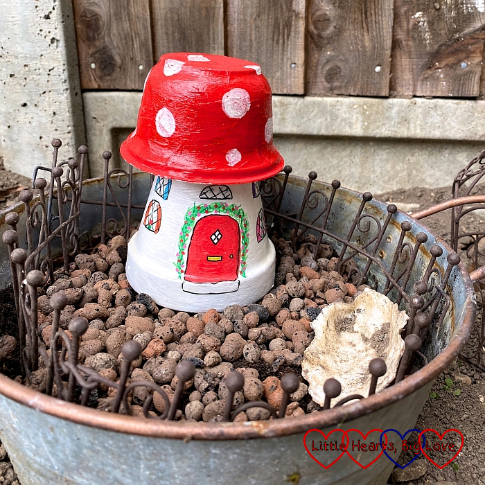 A hand-painted fairy house made from a flower pot with an upturned large yogurt pot on top for the roof