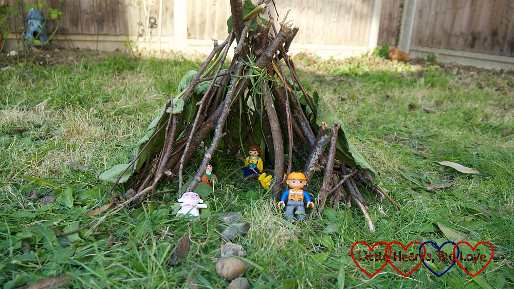 A toy den made of sticks with Playmobil 123 and Duplo figures inside