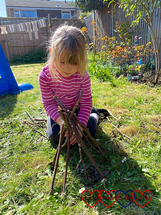 Sophie adding sticks to her mini den