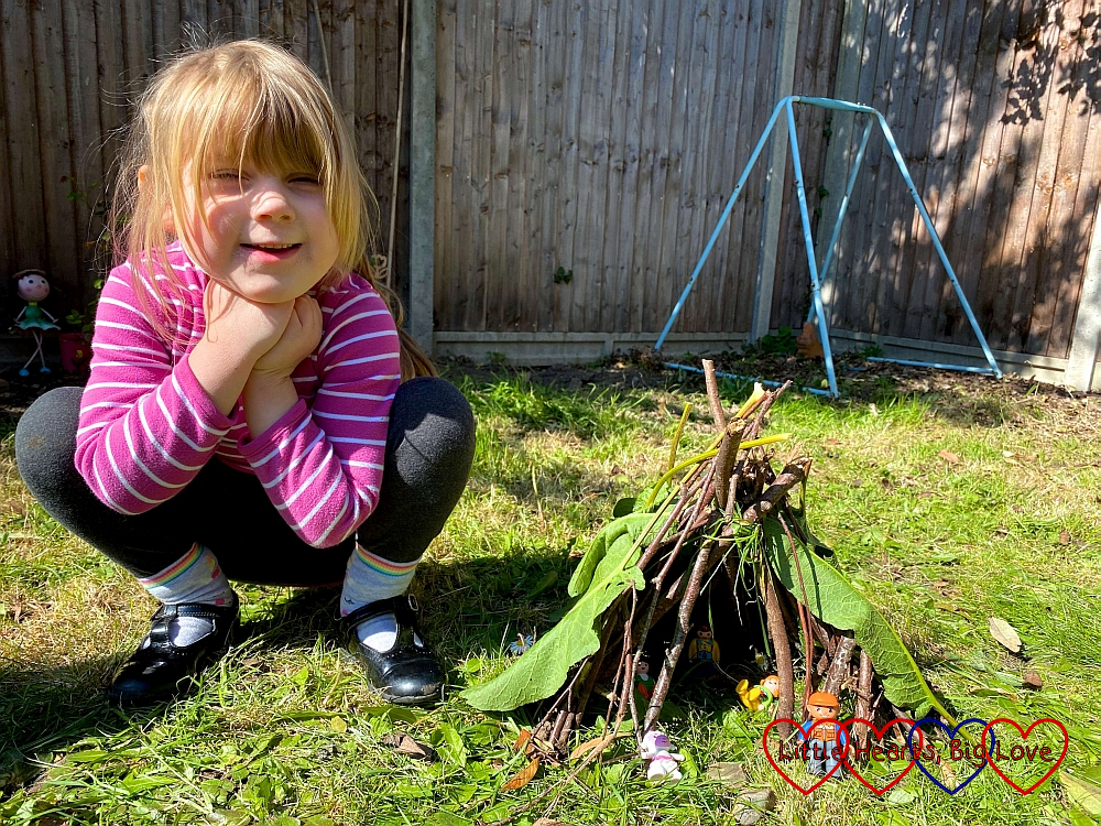 Sophie with her mini toy den made from sticks and covered in leaves with Duplo and Playmobil 123 figures inside