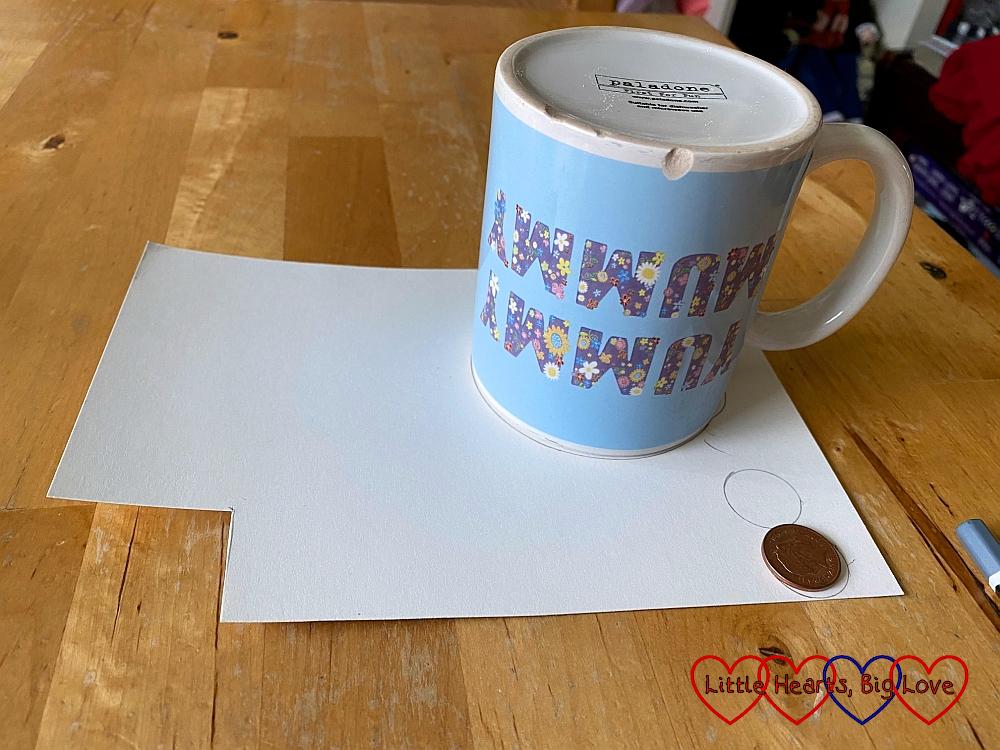 A mug and a penny on a piece of card