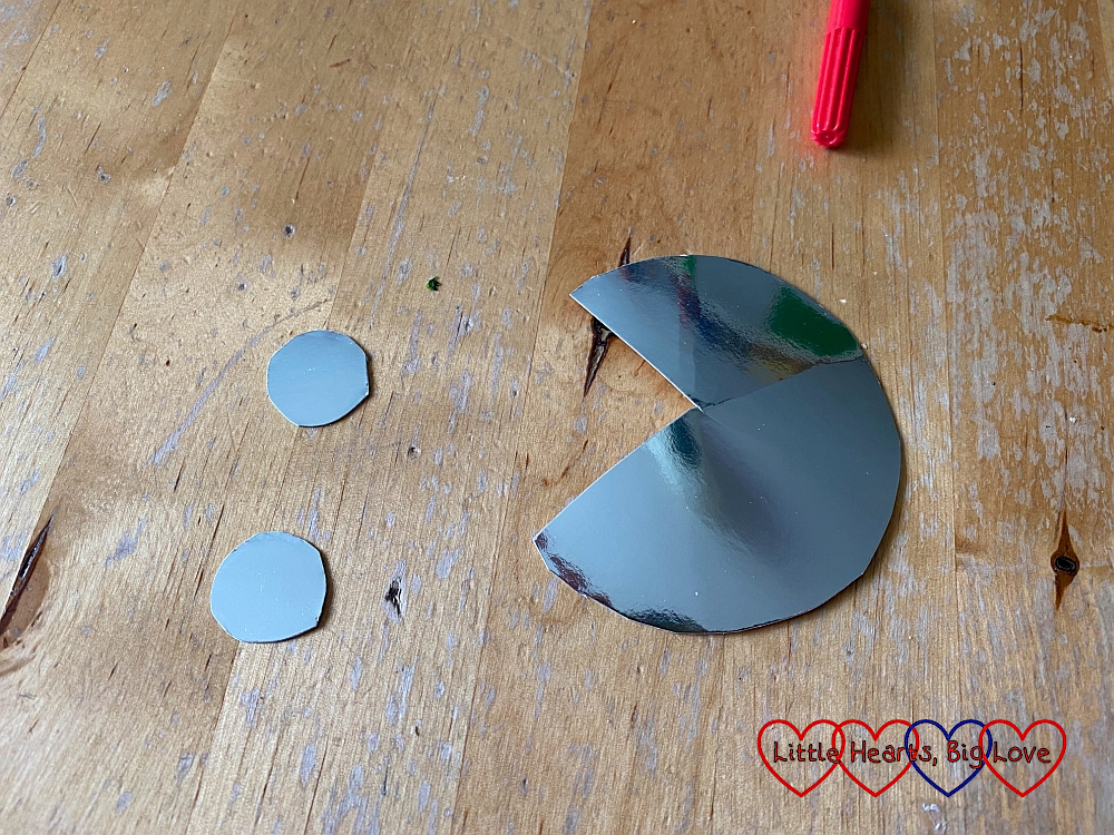 Two small circles and a large circle with a segment cut out, cut from silver card
